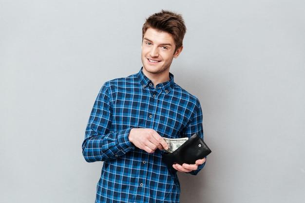 Homem feliz que está sobre a parede cinzenta que guarda a bolsa com dinheiro.