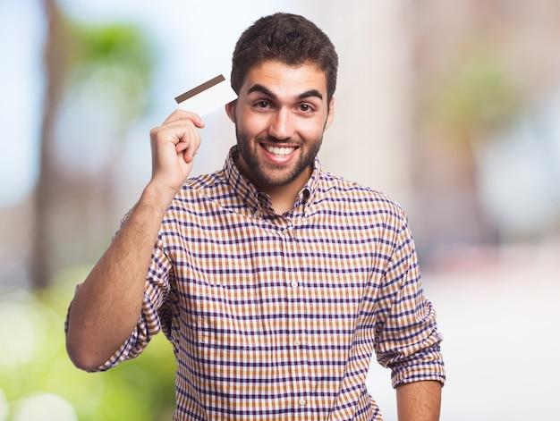 Homem feliz que prende o cartão de crédito.