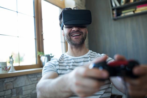 Homem feliz que usa auriculares realidade virtual e jogando vídeo game