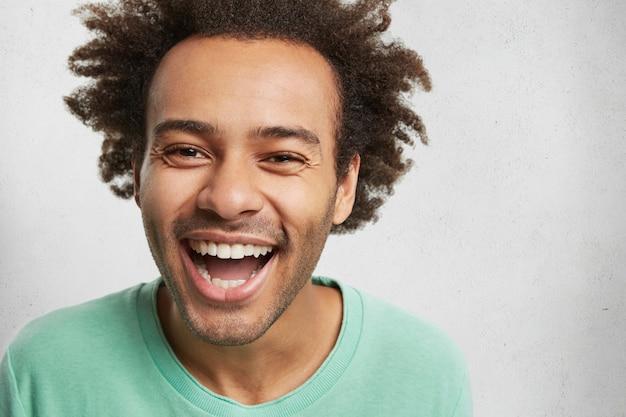Homem feliz radiante com pele escura e penteado espesso, sorri para a câmera e expressa emoções positivas