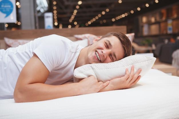 Homem feliz rindo, deitado em uma cama em loja de móveis