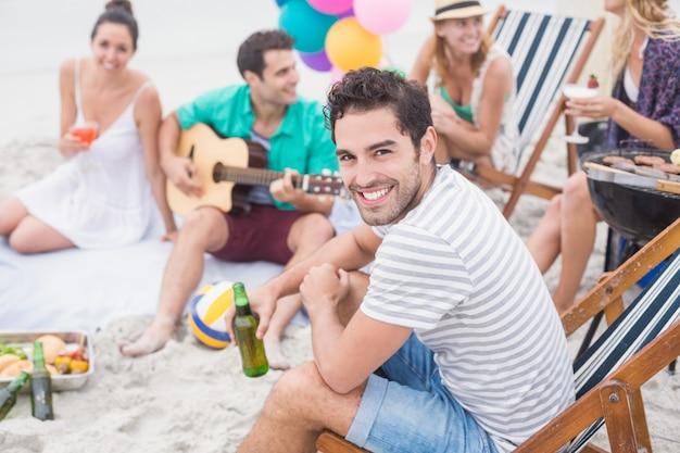 Homem feliz, segurando a cerveja e sorrindo enquanto está sentado com seus amigos