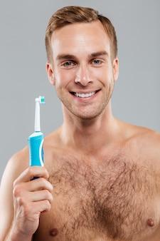 Homem feliz segurando a escova de dentes e olhando para a frente, isolado na parede cinza