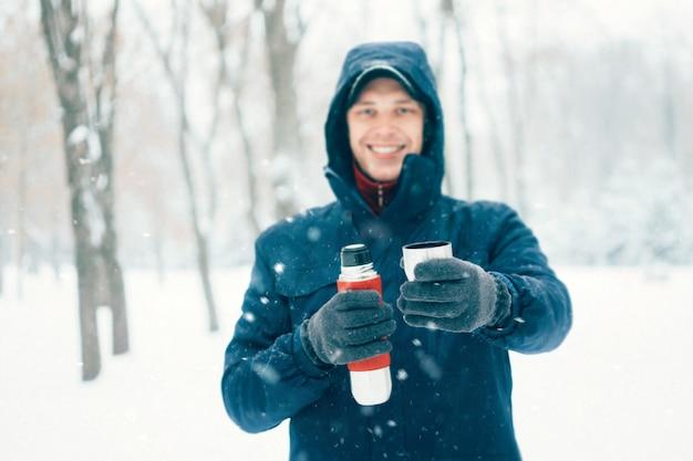 Homem feliz, segurando, garrafa térmica, em, inverno, parque