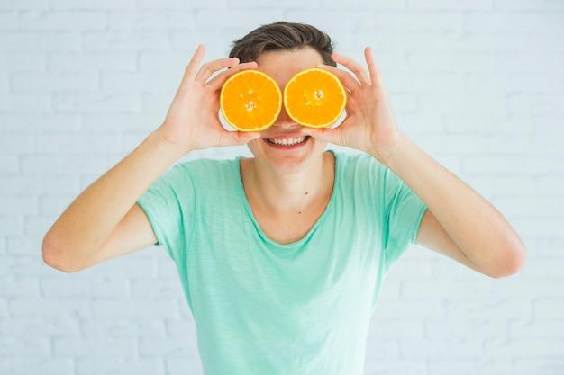 Homem feliz, segurando, halved, laranjas maduras, frente, seu, olhos