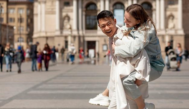 Homem feliz segurando mulher nas costas