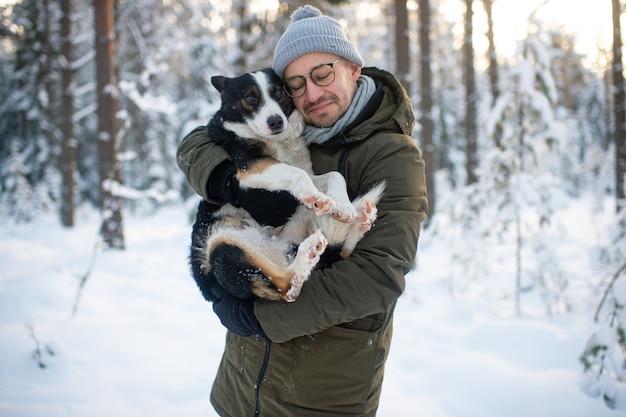 Homem feliz, segurando o cão adorável nas mãos no bosque nevado. menino de sorriso que abraça o filhote de cachorro adorável na madeira do inverno.