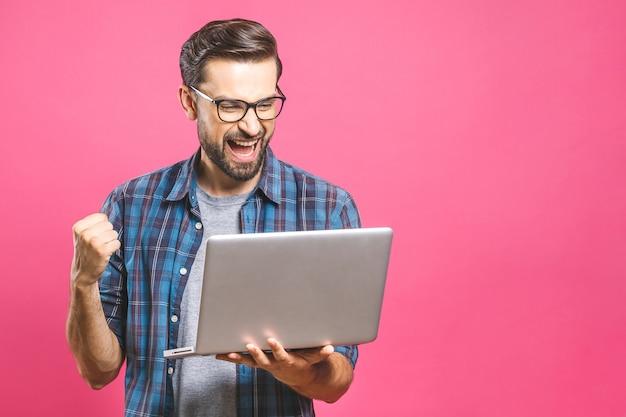 Homem feliz, segurando o laptop e comemorando seu sucesso