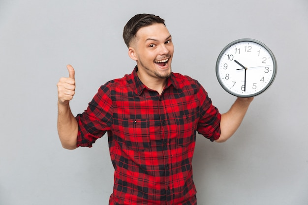 Homem feliz, segurando o relógio e aparecer o polegar