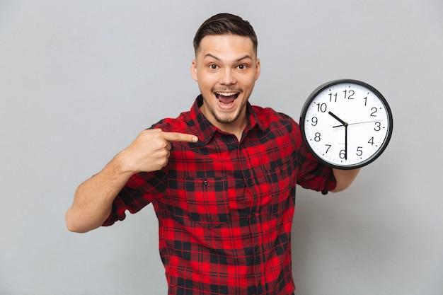 Homem feliz, segurando o relógio e apontando para os seus