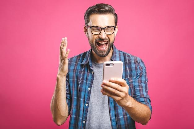 Homem feliz, segurando o smartphone e comemorando seu sucesso