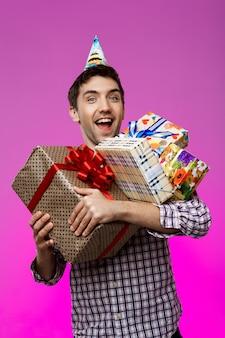 Homem feliz segurando presentes de aniversário em caixas sobre parede roxa.