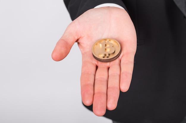 Homem feliz segurando um bitcoin grande e mostrando os polegares.