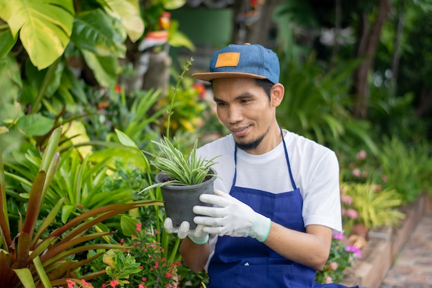 Homem feliz segurando um vaso de flores em uma loja de enfeites de jardim