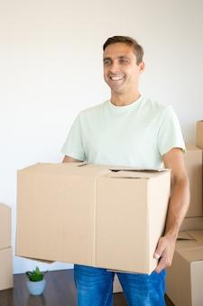 Homem feliz segurando uma caixa de papelão em seu novo apartamento ou casa