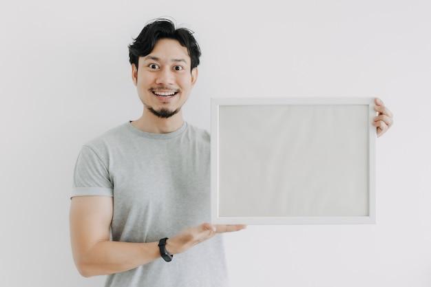 Homem feliz segurando uma moldura vazia isolada no fundo branco