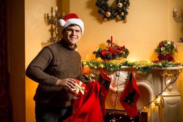 Homem feliz segurando uma sacola de papai noel vermelha com presentes na lareira