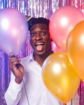 Homem feliz segurando uma vista frontal de balões