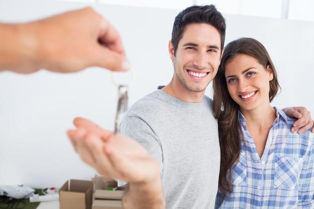 Homem feliz sendo dado uma chave de casa