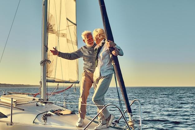 Homem feliz sênior apontando para o horizonte enquanto está com sua esposa na lateral de um barco a vela ou