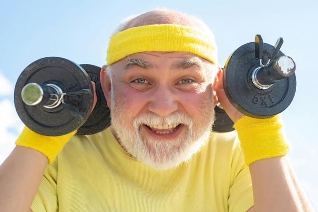 Homem feliz sênior fazendo exercícios com halteres