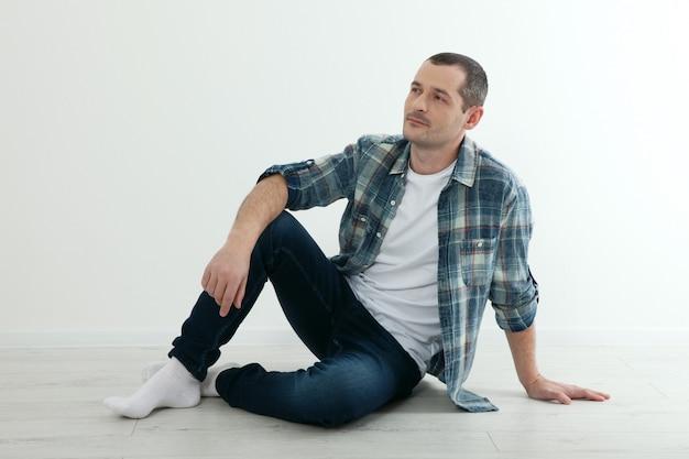 Homem feliz, sentada no chão em sua nova casa. conceito de isolamento