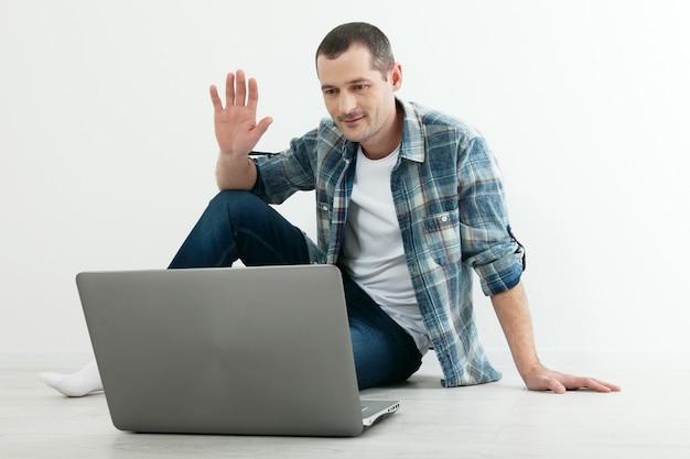 Homem feliz, sentada no chão em sua nova casa. trabalhe em casa conceito