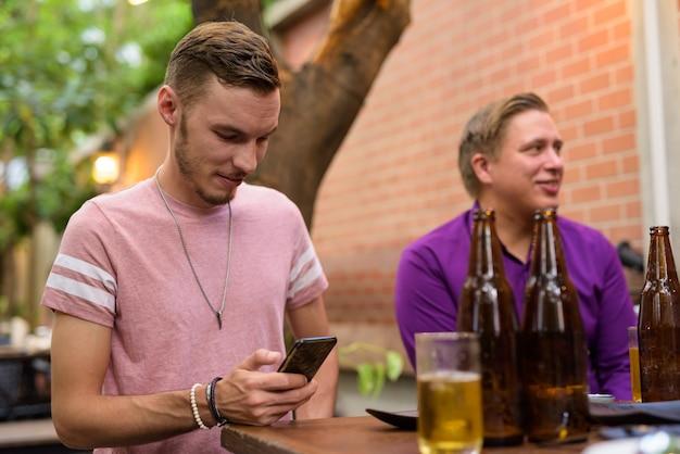 Homem feliz sentado a mandar mensagens de texto ao ar livre enquanto bebe cerveja