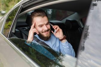 Homem feliz sentado dentro do carro falando no smartphone