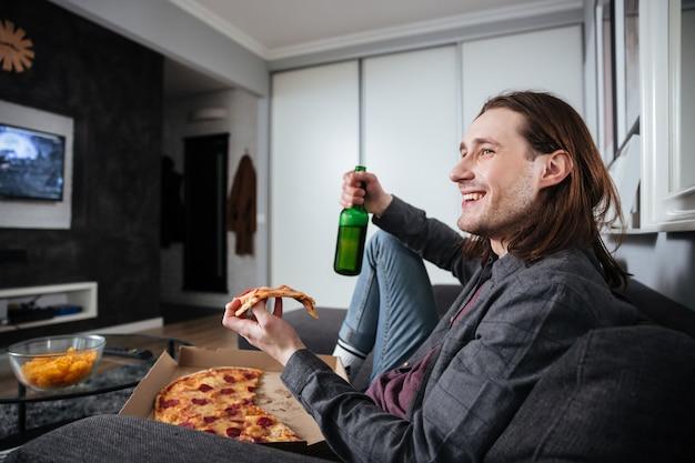 Homem feliz, sentado em casa, dentro de casa, comendo pizza
