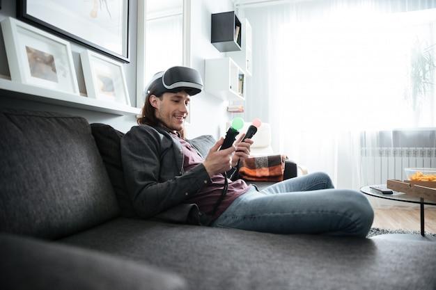 Homem feliz sentado em casa dentro de casa jogar jogos