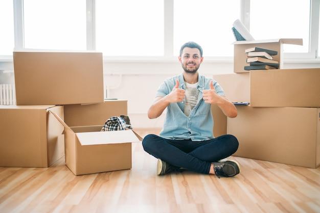 Homem feliz sentado em pose de ioga entre caixas de papelão, inauguração de casa. mudança para uma nova casa