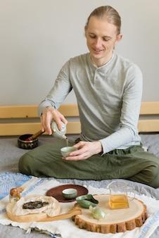 Homem feliz sentado na cama, fazendo a cerimônia do chá sozinho, fique em casa e esteja seguro durante o carantine. beber chá chinês