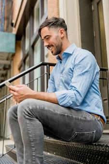 Homem feliz sentado na escada