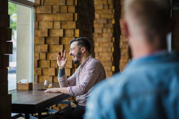 Homem feliz sentado no restaurante apreciando bebidas
