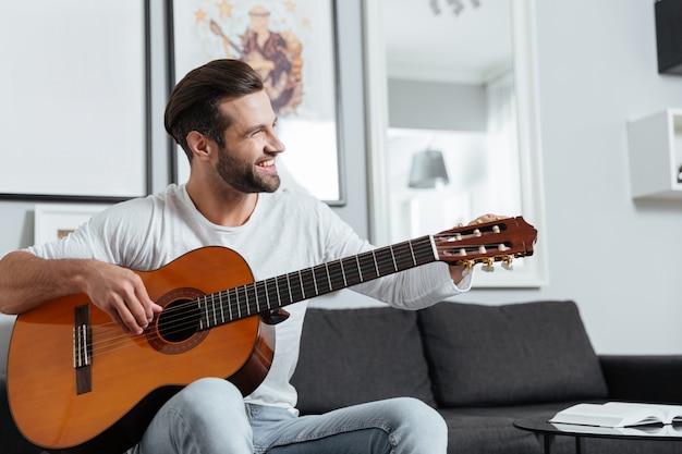 Homem feliz sentado no sofá tocando violão