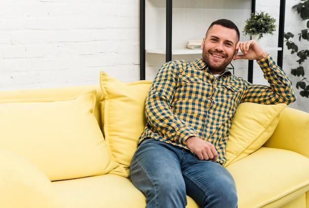 Homem feliz sentado no sofá