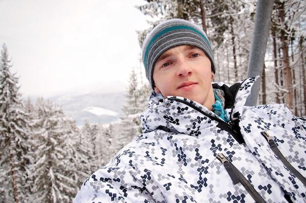 Homem feliz sobe no elevador nas montanhas dos cárpatos. fechar-se. natureza do inverno. queda de neve forte.
