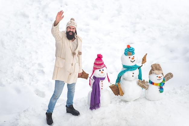 Homem feliz sorridente sno dia ensolarado de inverno com pai feliz. pai fazendo família do homem da neve para