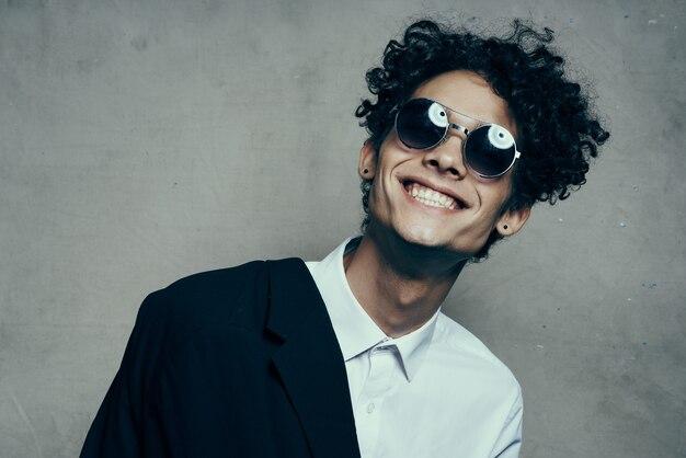 Homem feliz sorriso deslumbrante cabelo encaracolado óculos modelo camisa jaqueta