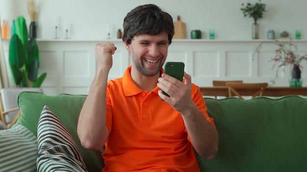 Homem feliz surpreso segurando um telefone olhando para o celular lendo uma boa notícia em sms no sofá