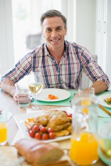 Homem feliz, tendo a refeição na mesa de jantar