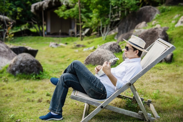 Homem feliz tocar guitarra no jardim da natureza verde