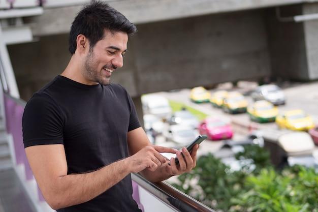 Homem feliz usando aplicativo de smartphone em trânsito intenso