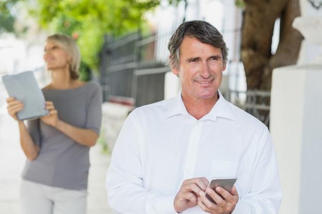 Homem feliz usando celular com mulher no fundo