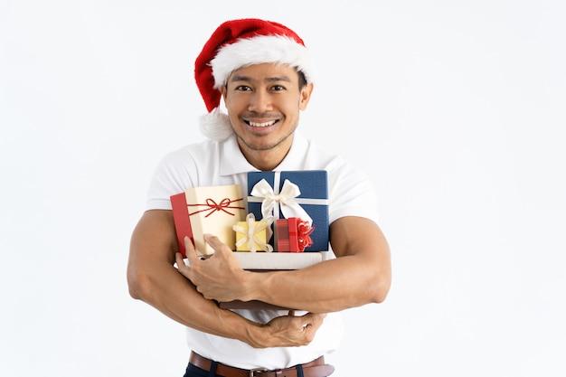 Homem feliz usando chapéu de papai noel e abraçando caixas de presente