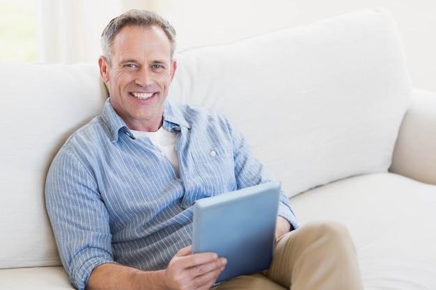 Homem feliz usando computador tablet na sala de estar