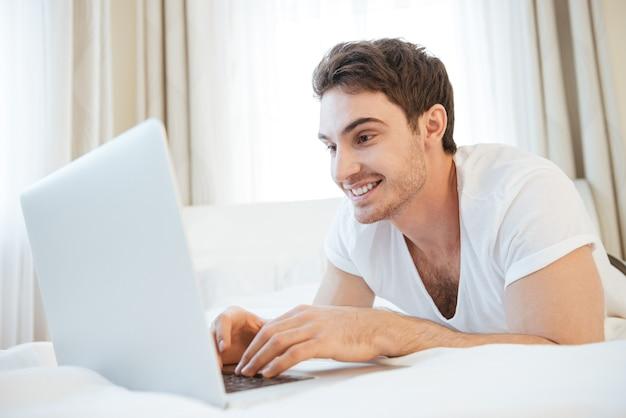 Homem feliz usando laptop e deitado na cama. vista lateral