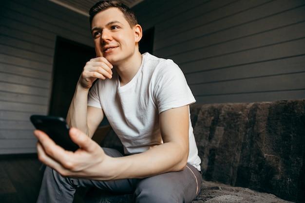 Homem feliz usando o telefone enquanto está sentado no sofá em sua casa moderna. conceito de jovens trabalhando em dispositivos móveis.