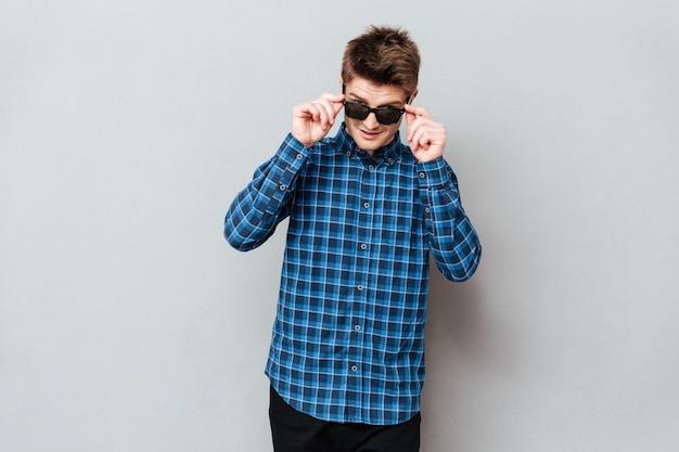 Homem feliz, usando óculos escuros em cima de parede cinza